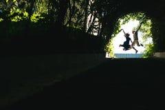 couplez sauter à la fin de tunnel avec des arbres Image stock