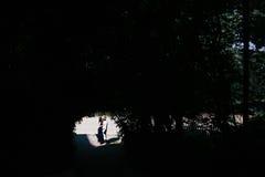 couplez sauter à la fin de tunnel avec des arbres Photographie stock libre de droits