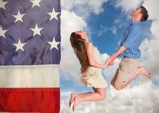 Couplez sauter dans le ciel contre le drapeau américain Photos libres de droits