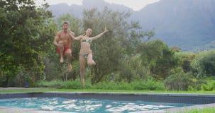 Couplez sauter ensemble dans la piscine à la station de vacances 4k clips vidéos