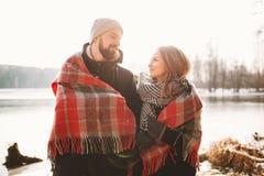 Couplez se regarder près du lac d'hiver sous le plaid Photo stock