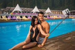 Couplez se reposer au bord de la piscine à la station de vacances et prendre la photo de selfie au téléphone avec le bâton de sel Image libre de droits