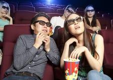 Couplez se reposer au cinéma, observant un film d'horreurs Photographie stock libre de droits