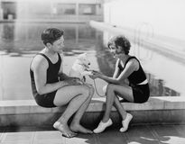 Couplez se reposer avec leur chiot à côté d'une piscine (toutes les personnes représentées ne sont pas plus long vivantes et aucu Photo libre de droits