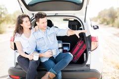 Couplez se reposer dans le tronc de voiture et regarder une vue Image libre de droits