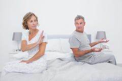 Couplez se reposer de différents côtés du lit ayant un argument photographie stock