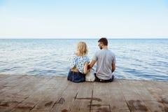 Couplez se reposer de nouveau à l'appareil-photo avec le bouledogue français près de la mer Image libre de droits