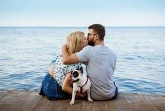 Couplez se reposer de nouveau à l'appareil-photo avec le bouledogue français près de la mer Photo stock