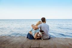 Couplez se reposer de nouveau à l'appareil-photo avec le bouledogue français près de la mer Photos stock