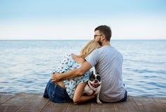 Couplez se reposer de nouveau à l'appareil-photo avec le bouledogue français près de la mer Photographie stock