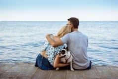 Couplez se reposer de nouveau à l'appareil-photo avec le bouledogue français près de la mer Image stock