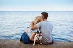 Couplez se reposer de nouveau à l'appareil-photo avec le bouledogue français près de la mer Images libres de droits