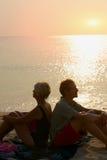 Couplez se reposer de nouveau au dos sur la plage au coucher du soleil Images libres de droits