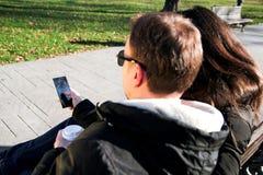 Couplez se reposer en parc au café regardant le téléphone portable Photographie stock