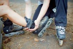 Couplez se reposer en parc dans des patins de rouleau Images libres de droits