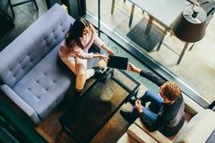 Couplez se reposer ensemble et à l'aide d'un comprimé, la vue franc Image stock