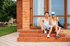 Couplez se reposer et étreindre sur le porche de la maison Images libres de droits