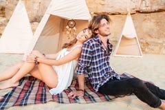 Couplez se reposer et détendre près du tipi sur la plage Photographie stock