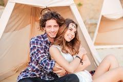 Couplez se reposer et embrasser dans le tipi sur la plage Photographie stock libre de droits