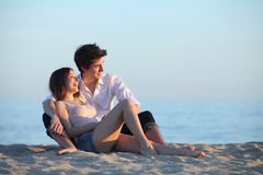 Couplez se reposer et rire sur le sable de la plage au coucher du soleil Image libre de droits