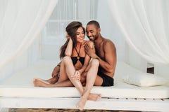 Couplez se reposer et sourire dans le lit blanc sur la plage Photographie stock libre de droits