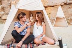 Couplez se reposer et sourire dans le tipi sur la plage Photos libres de droits