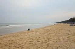 Couplez se reposer et voyez le téléphone portable sur la plage dans le ciel de matin, Cha-suis plage, Phetchaburi, Thaïlande, Photographie stock