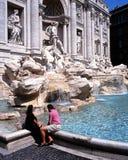 Couplez se reposer par la fontaine de TREVI, Rome Image stock