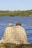 Couplez se reposer par un bord de lac avec la couverture autour des épaules Photographie stock libre de droits