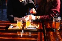 Couplez se reposer près de la table avec le bouillon de mer-nerprun dans le discu de café Photos stock