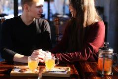 Couplez se reposer près de la table avec le bouillon de mer-nerprun dans le discu de café Images libres de droits