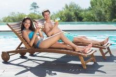 Couplez se reposer sur des canapés du soleil par la piscine Photographie stock