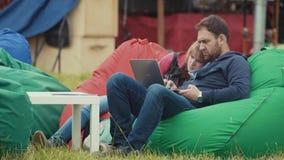 Couplez se reposer sur des chaises de fauteuil poire sur la pelouse d'herbe en parc de ville avec l'ordinateur portable banque de vidéos