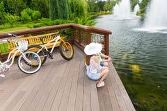 Couplez se reposer sur la plate-forme en bois après avoir fait du vélo Photographie stock libre de droits
