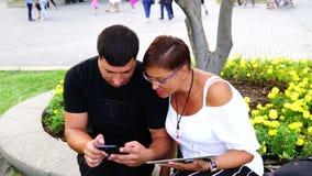 Couplez se reposer sur le banc dans le jardin et à l'aide du comprimé et du smartphone Ils regardent dans l'appareil-photo banque de vidéos