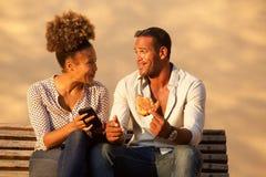 Couplez se reposer sur le banc de parc avec le téléphone portable et le casse-croûte image libre de droits