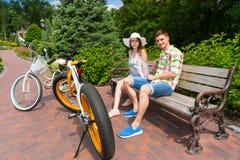 Couplez se reposer sur le banc près des vélos en beau parc vert Photo stock