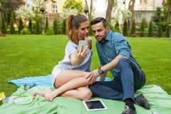 Couplez se reposer sur le blaket, passer le temps gentil et prendre l'individu Photo libre de droits