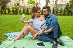 Couplez se reposer sur le blaket, passer le temps gentil et prendre l'individu Image stock