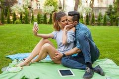 Couplez se reposer sur le blaket, passer le temps gentil et prendre l'individu Photographie stock