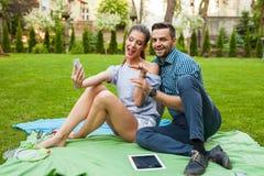 Couplez se reposer sur le blaket, passer le temps gentil et prendre l'individu Images stock