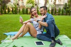 Couplez se reposer sur le blaket, passer le temps gentil et prendre l'individu Photo stock