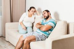 Couplez se reposer sur le divan à la maison dans le salon photos libres de droits