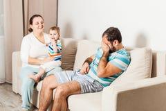 Couplez se reposer sur le divan à la maison et parler images stock