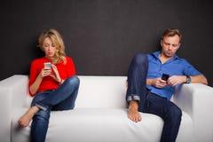 Couplez se reposer sur le divan avec leurs téléphones dans leur main Photo libre de droits
