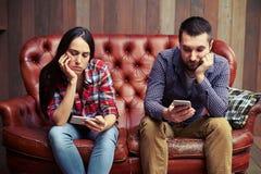 Couplez se reposer sur le divan regardant leurs téléphones Photos stock