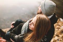 Couplez se reposer sur le pilier au lac congelé regardant l'un l'autre photo libre de droits