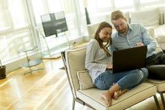 Couplez se reposer sur le plancher avec l'ordinateur portable dans le salon image libre de droits