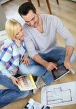 Couplez se reposer sur le plancher regardant le comprimé pour choisir des murs de couleurs Image libre de droits