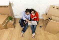 couplez se reposer sur le plancher se déplaçant la nouvelle maison choisissant des meubles avec l'ordinateur portable d'ordinateu Photographie stock